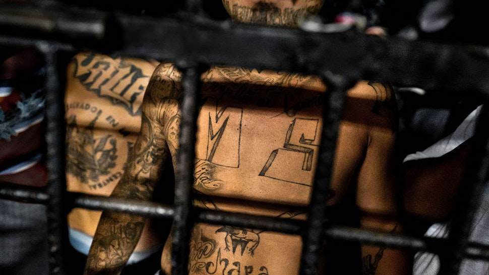 A member of the Mara Salvatrucha gang (MS-13) stands behind bars in a cell at a detention center on February 20, 2014 in San Salvador, El Salvador. Although the country's two major gangs reached a truce in 2012, the police holding cells currently house more than 3000 inmates, five times the official capacity. Partly because Mara gang members did not break with their criminal activities, partly because Salvadorean police still applies a controversial anti-gang law which allows to detain almost anyone for suspicion of gang membership. Accused young men are held in police detention centers where up to 25 inmates may share a cell of five square metres. In the dark overcrowded cages, under harsh and life-threatening conditions, suspected gang members wait for trial or for to be transported to a regular prison. (Photo by Jan Sochor/LatinContent/Getty Images)