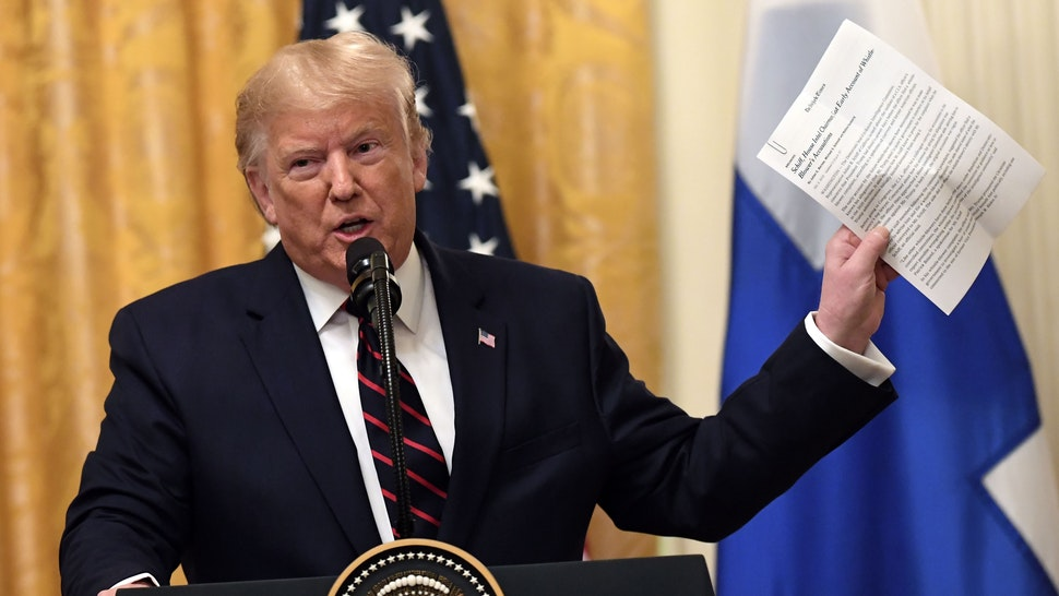 US President Donald Trump holds up a NYTimes report on House Intelligence Committee chairman Adam Schiff as he and Finnish President Sauli Niinisto(not shown) hold a joint press conference in the East Room of the White House in Washington, DC, on October 2, 2019.