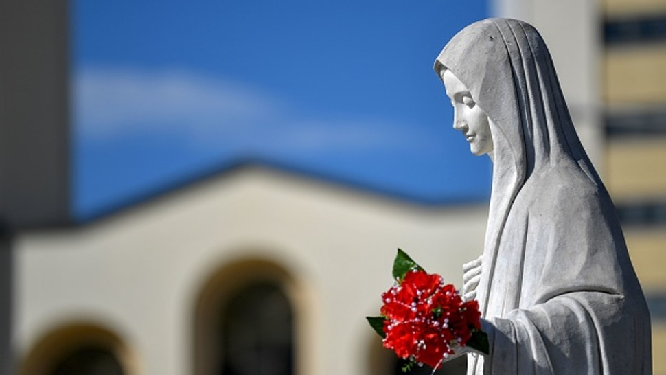 This picture taken on June 26, 2019 shows a statue of Virgin Marry, in front of Franciscan church of St. Jacob, in Southern-Bosnian village of Medjugorje. - The Bosnian town of Medjugorje has become an unofficial site of Catholic pilgrimage since the supposed apparition of Virgin Mary in front of children on a nearby hill, 38 years ago. According to some of the pilgrims, Medjugorje is as sacred as Lourdes or Fatima.