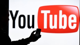 - A man with Smartphone stands before the Logo of the Internet platform YouTube. Photo: Carsten Rehder/dpa (Photo by Carsten Rehder/picture alliance via Getty Images)