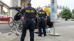 Two Bay Area Rapid Transit (BART) police officers are viewed from behind, with an overturned bicycle and bag with sorted contraband on the sidewalk in front of the officers, in the San Francisco Bay Area town of Daly City, California, November 3, 2017.