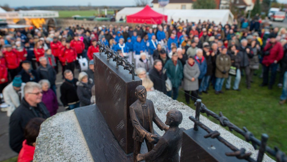 11 November 2019, Saxony-Anhalt, Stapelburg: Participants of a festive event stand at the border monument. There people celebrated the fall of the wall 30 years ago. The border in Stapelburg had been opened on 11 November 1989. Photo: Klaus-Dietmar Gabbert/dpa-Zentralbild/dpa (Photo by Klaus-Dietmar Gabbert/picture alliance via Getty Images)