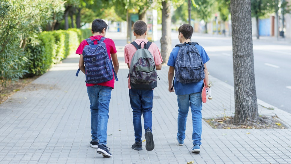 Rear view of friends with backpacks walking on sidewalk in city