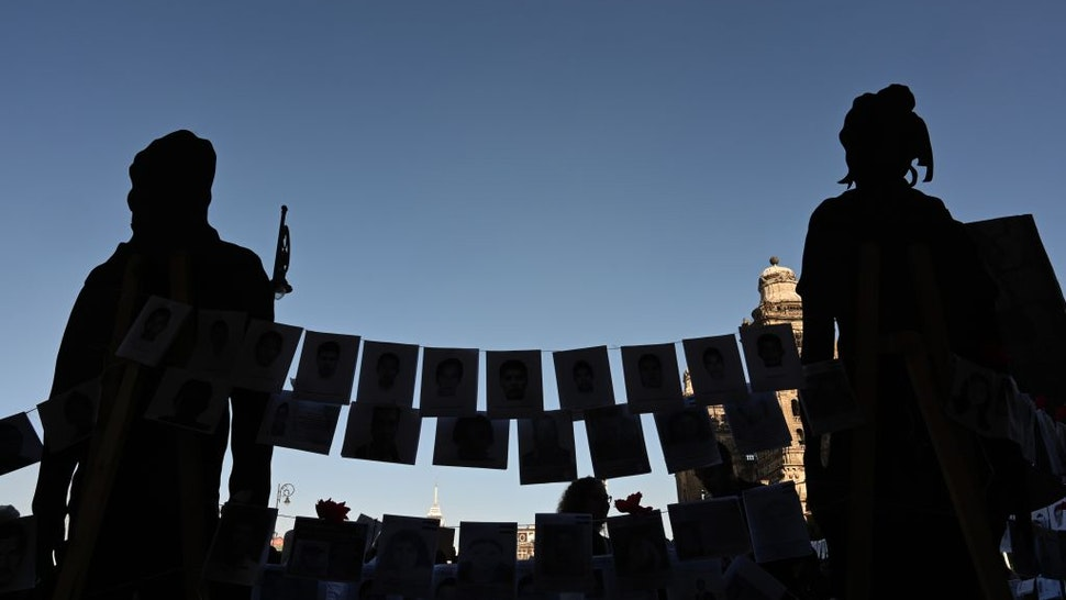 Pictures of missing persons hang from a rope in front of the National Palace during the commemoration of the International Day of the Disappeared in Mexico City, on August 30, 2019. - More than 40,000 people are missing in Mexico, which has been swept by a wave of violence since the government declared war on the country's powerful drug cartels in 2006. (Photo by RODRIGO ARANGUA / AFP) (Photo credit should read RODRIGO ARANGUA/AFP via Getty Images)