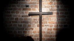 An old wooden cross can be seen in a sunspot on the wall of the market church during the church service on Reformation Day. Reformation Day is the third holiday in Lower Saxony. Photo: Peter Steffen/dpa (Photo by Peter Steffen/picture alliance via Getty Images)