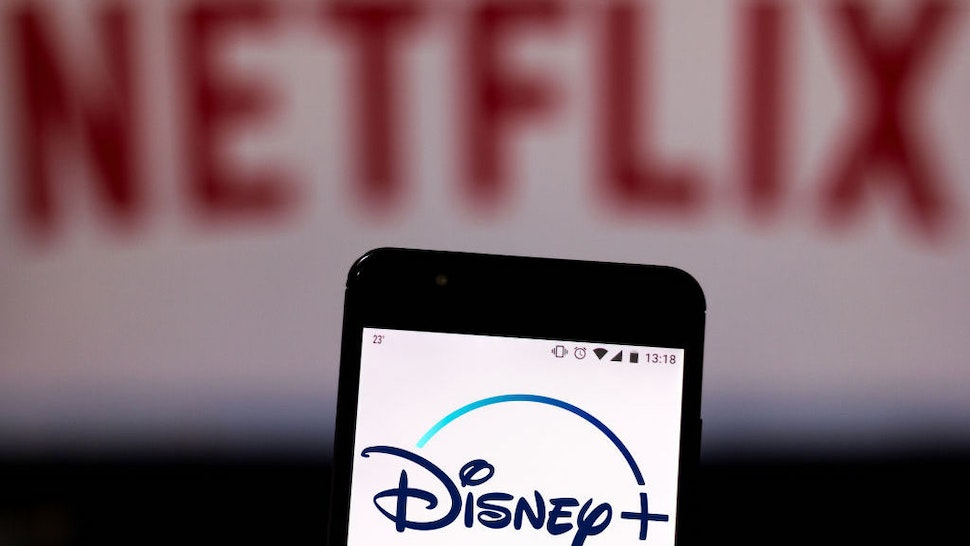 In this photo illustration the Disney Plus logo is seen displayed on a smartphone and logo Netflix on the blurred background. (Photo Illustration by Rafael Henrique/SOPA Images/LightRocket via Getty Images)