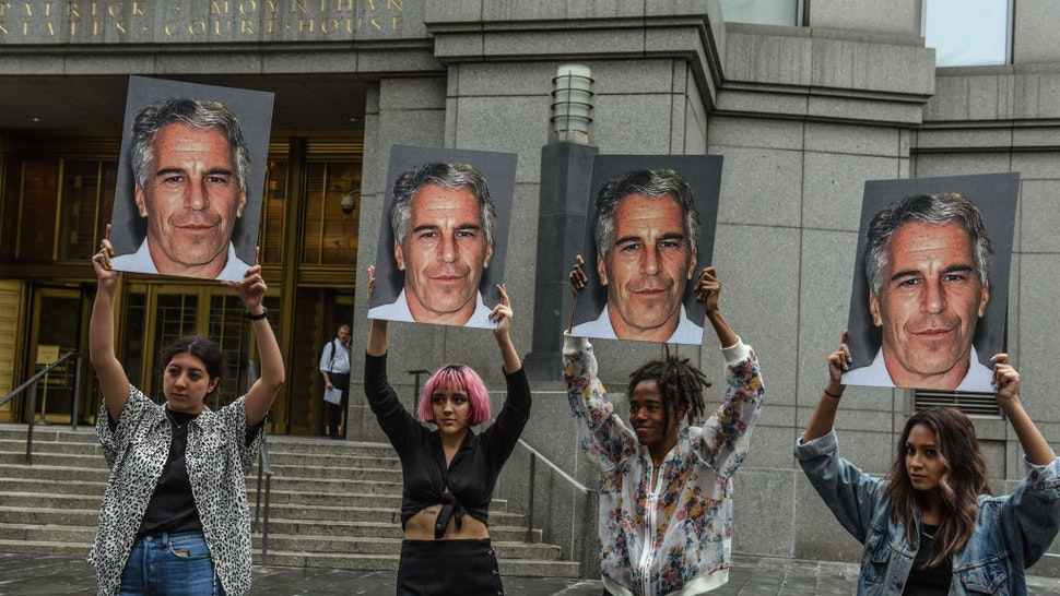 """A protest group called """"Hot Mess"""" hold up signs of Jeffrey Epstein in front of the Federal courthouse on July 8, 2019 in New York City. According to reports, Epstein will be charged with one count of sex trafficking of minors and one count of conspiracy to engage in sex trafficking of minors. (Photo by Stephanie Keith/Getty Images)"""