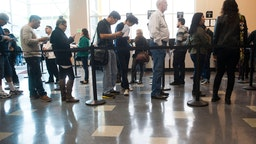 Richard Taylor, of Huntington Beach, third from right, patiently waits in line to get his driver's license renewed at the crowded new DMV office in Stanton Saturday.