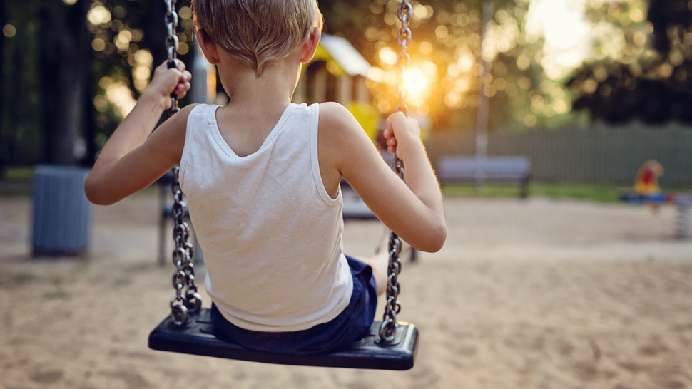 Young boy on swing - stock photo