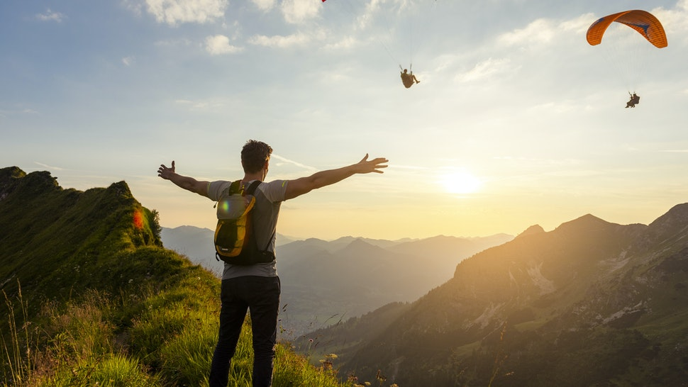 Germany, Bavaria, Oberstdorf, man on a hike in the mountains at sunset with paraglider in background