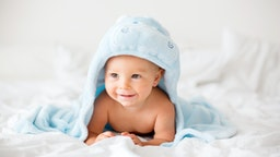 Cute little baby boy, relaxing in bed after bath, smiling happily, daytime