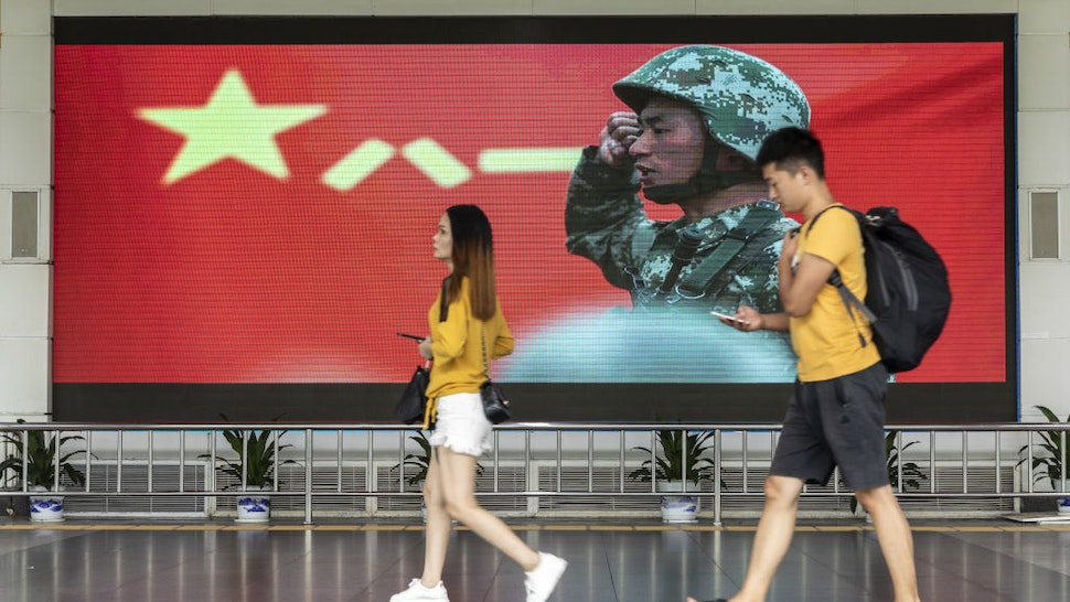 Pedestrians walk past an advertisement for the People's Liberation Army (PLA) on a screen near the Luohu border crossing in Shenzhen, China, on Thursday, Aug. 15, 2019.