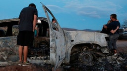Members of the Lebaron family look at the burned car where part of the nine murdered members of the family were killed and burned during an ambush in Bavispe, Sonora mountains, Mexico, on November 5, 2019.