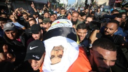 Mourners chant slogans as they carry the body of Palestinian Islamic Jihad senior leader Baha Abu Al-Ata during his funeral in Gaza City on November 12, 2019.
