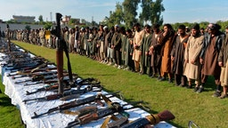 In this photograoh taken on November 17, 2019 members of the Islamic State (IS) group stand alongside their weapons, following they surrender to Afghanistan's government in Jalalabad, capital of Nangarhar Province.