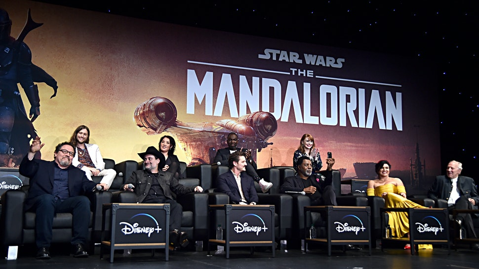 """HOLLYWOOD, CALIFORNIA - NOVEMBER 13: (L-R) Executive Producer Jon Favreau, Composer Ludwig Göransson, Executive Producer/Director Dave Filoni, Director Deborah Chow, Pedro Pascal, Rick Famuyiwa, Carl Weathers, Director Bryce Dallas Howard, Gina Carano and Werner Herzog speak onstage at the premiere of Lucasfilm's first-ever, live-action series, """"The Mandalorian,"""" at the El Capitan Theatre in Hollywood, Calif. on November 13, 2019. """"The Mandalorian"""" streams exclusively on Disney+. (Photo by Alberto E. Rodriguez/Getty Images for Disney)"""