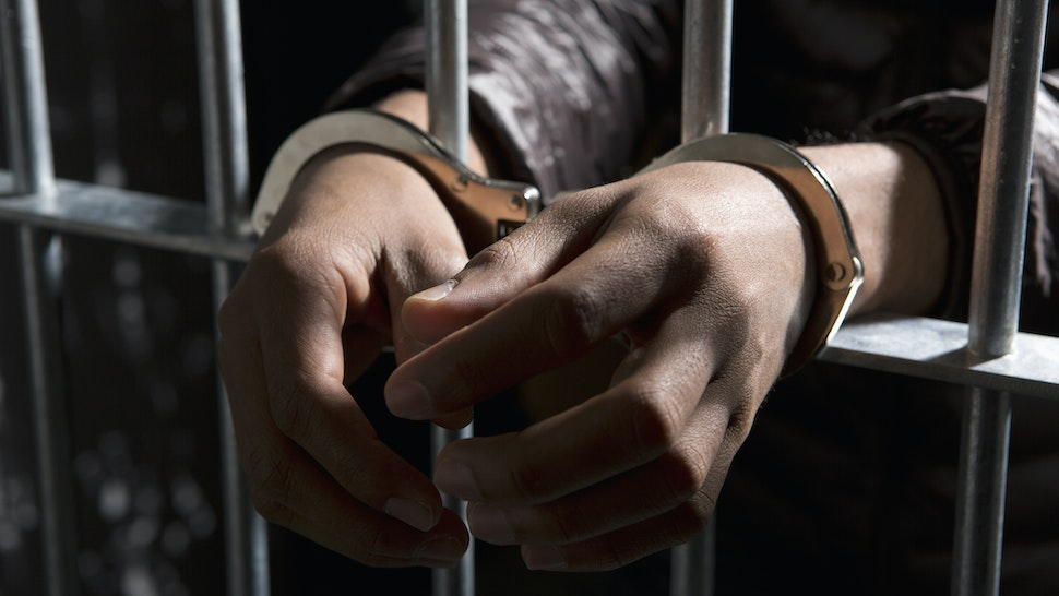 A prisoner behind bars with hands cuffed - stock photo
