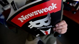 This photo illustration shows a man reading a copy of the new print edition of Newsweek magazine in Washington on March 10, 2014. Newsweek, online only since the end of 2012, returned to print on March 7 in the United States and Europe. Parent company IBT Media is taking a gamble in re-launching the once-iconic news weekly, which has nearly disappeared in the face of serious financial difficulties. In crafting its print resurrection, the New York-based online media group, led by French businessman Etienne Uzac, has adopted a strategy that goes against current practices. The new magazine will seek to position itself as a high-end product, in particular with higher quality paper and printing than its competitors.