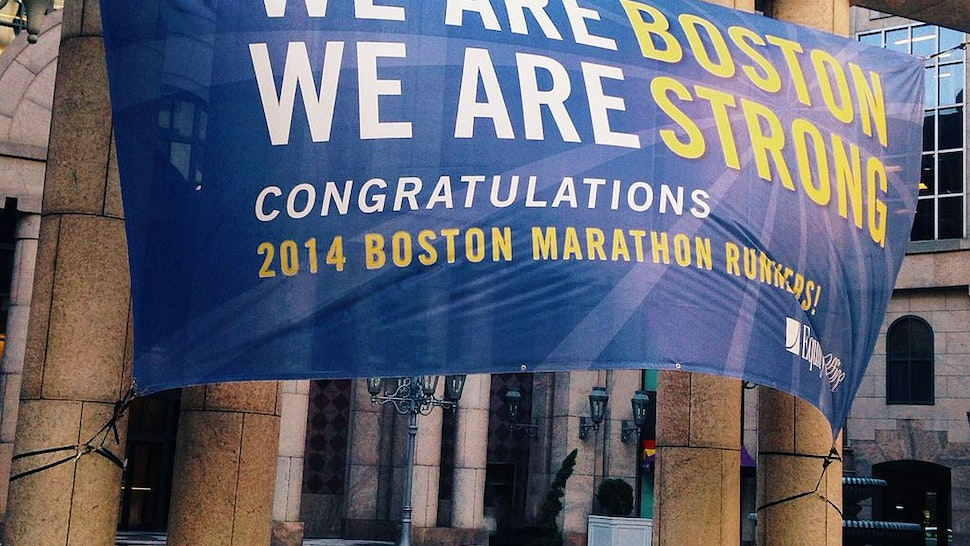 A banner honoring the 2014 Boston Marathon is strung from pillars on Boylston Street and strains in a strong wind.