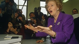 Margaret Thatcher plays up to the media at a North London school in her own constituency of Finchley during the 1992 general election. Although Thatcher had already resigned as Prime Minister in November 1990, John Major won the ensuing leadership election later that year. Photographers and cameramen surround the former-Prime Minister who is wearing a purple suit and matching broach. She is mid-sentence and has found something amusing to respond to the chants of the media. We see cameras, sound booms and flashes all prepared to photograph this famous statesman including Tom Stoddart who is making eye-contact with the viewer. (Photo by In Pictures Ltd./Corbis via Getty Images)