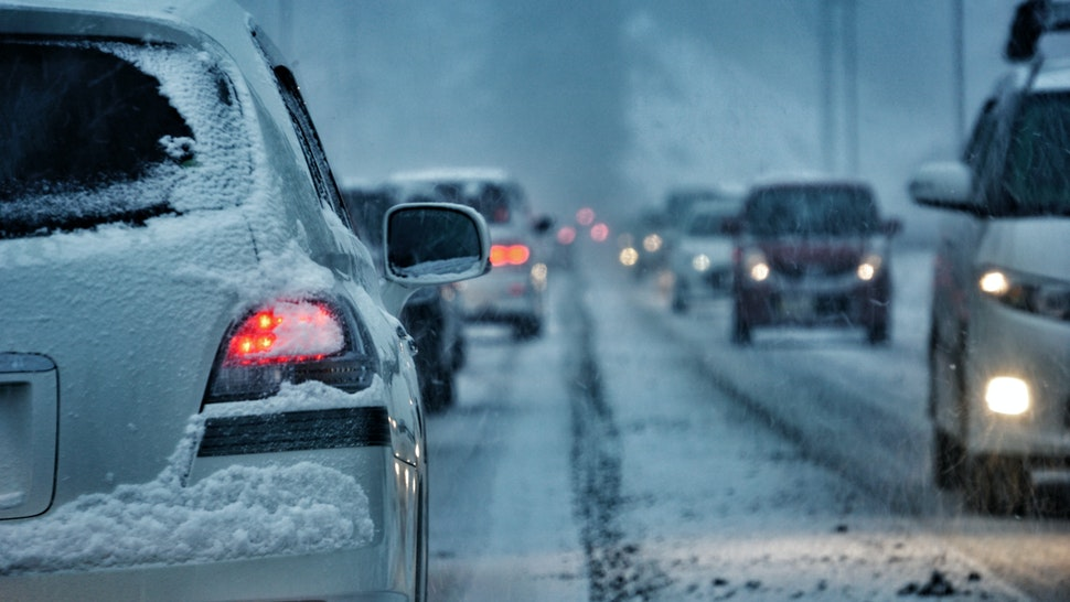 Vehicles On Street During Snowfall - stock photo