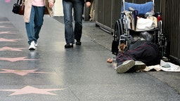 In this 16 October 2006 file photo, a homeless man sleeps on the walk of stars on Hollywood Boulevard in Hollywood, California.