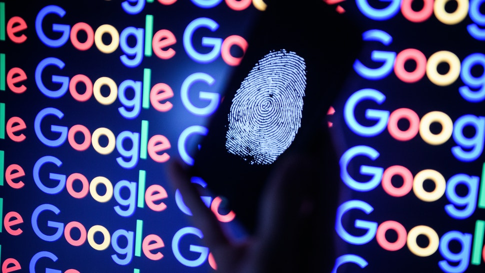 In this photo illustration, A thumbprint is displayed on a mobile phone while the Google logo is displayed on a computer monitor on August 09, 2017 in London, England. Founded in 1995 by Sergey Brin and Larry Page, Google now makes hundreds of products used by billions of people across the globe, from YouTube and Android to Smartbox and Google Search.
