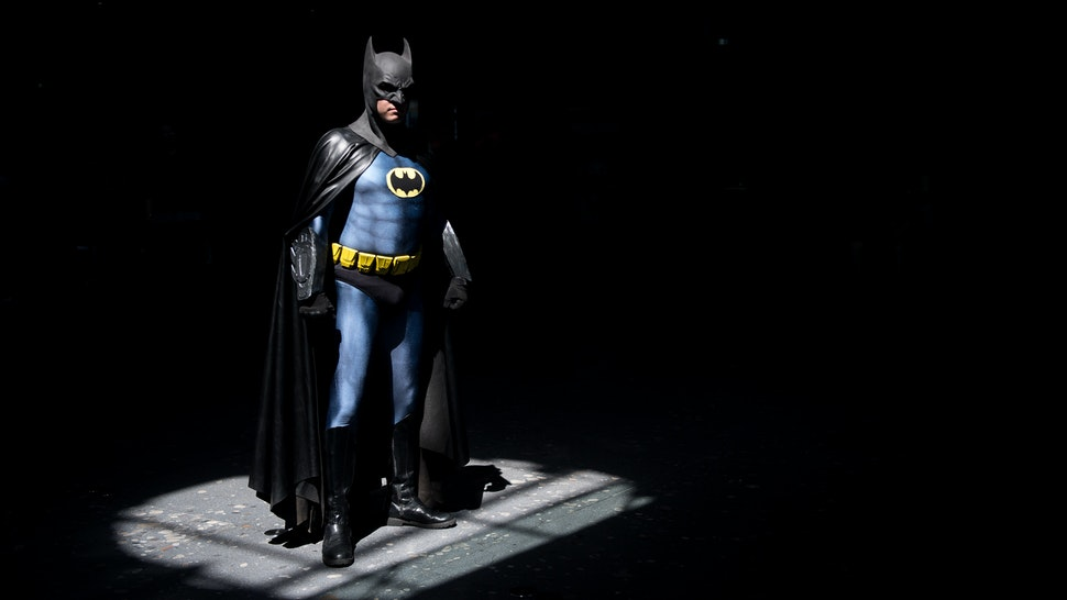 """30 June 2018, Germany, Stuttgart: A cosplayer wearing a batman outfit standing in the spotlight during the first day of the pop culture fair """"Comic Con Germany"""" at the Stuttgart trade fair. The fair is taking place from 30 June to 01 July. Photo: Sebastian Gollnow/dpa (Photo by Sebastian Gollnow/picture alliance via Getty Images)"""