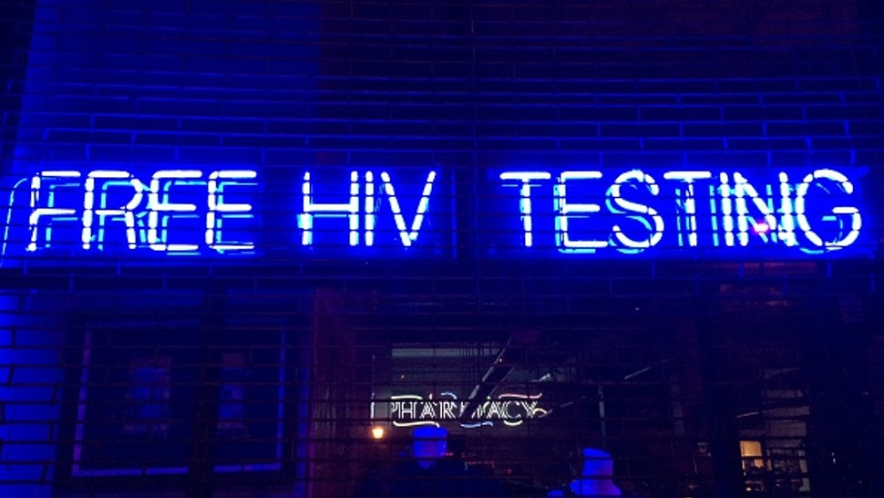 'Free HIV Testing' is spelled out in blue & white neon letters hanging in a storefront window behind security gates in Boerum Hill, Brooklyn, NYC - March 9, 2015