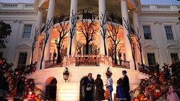 WASHINGTON, DC - OCTOBER 28: U.S. President Donald Trump and first lady Melania Trump hand out candy to trick-or-treaters during a Halloween at the White House event at the South Portico of the White House October 28, 2019 in Washington, DC.