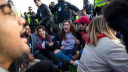 NEW HAVEN, CT - NOVEMBER 23: Harvard and Yale students protest during the halftime of the college football game between Harvard and Yale at the Yale Bowl in New Haven, CT on Saturday, Nov. 23, 2019. Demonstrators stormed the field during halftime at the Harvard-Yale football game Saturday, delaying the game for about an hour to demand that both universities divest their investments in fossil fuels and to call attention to the issue of climate change. The protest, which began with a few dozen protesters staging a sit-in midfield as the Yale band finished its halftime routine, swelled to about 500 people at one point as others in the stands joined the demonstration.