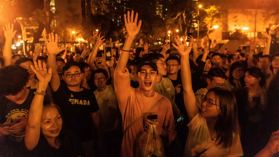 "HONG KONG, CHINA - NOVEMBER 25: Local residents celebrate as Junius Ho Kwan-yiu loses in District Council Elections, outside a polling station on November 25, 2019 in Hong Kong, China. Hong Kong held its district council election on Sunday as anti-government protests continue into its sixth month with demands for an independent inquiry into police brutality, the retraction of the word ""riot"" to describe the rallies, and genuine universal suffrage."