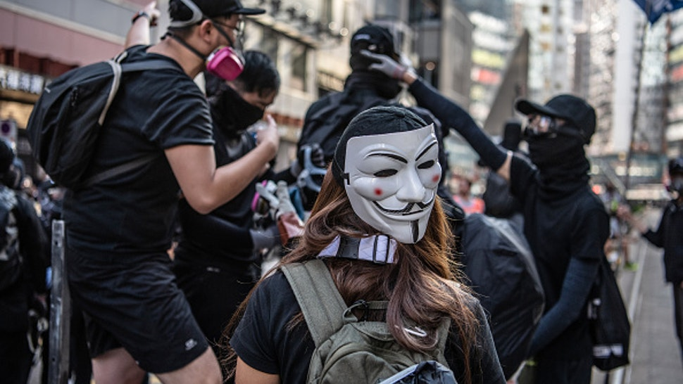 A demonstrator wears an anonymous masks, also known as Guy Fawkes masks, on the back of her head during a protest on Hennessy Road in the Causeway Bay district of Hong Kong, China, on Saturday, Nov. 2, 2019. Hong Kong police fired multiple rounds of tear gas at protesters who rallied for a 22nd consecutive weekend despite authorities denying them a permit to gather.