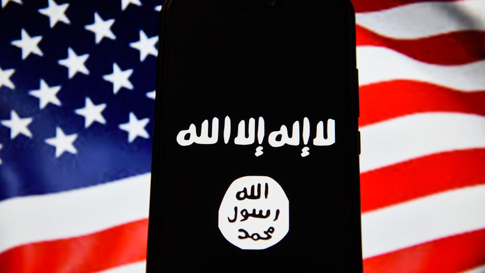 In this photo illustration, the Islamic State flag is seen displayed on an Android mobile phone with United States of America flag in the background. (Photo Illustration by Omar Marques/SOPA Images/LightRocket via Getty Images)