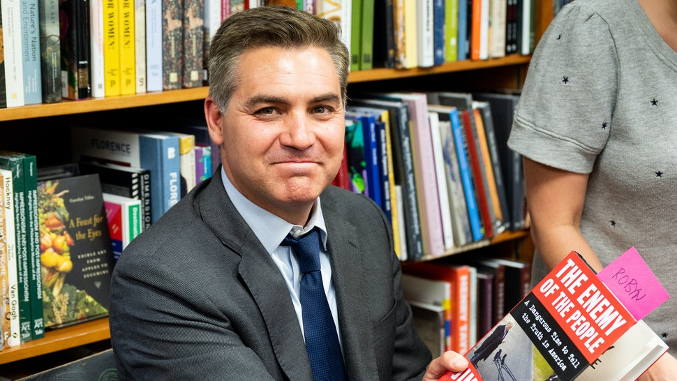 "WASHINGTON, D C , UNITED STATES - 2019/06/18: Jim Acosta holds his book ""The Enemy of the People: A Dangerous Time to Tell the Truth in America"" at the Politics and Prose bookstore in Washington, DC."