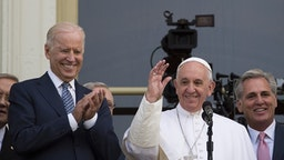 Pope Francis (C) waves, next to US Vice President Joe Biden(L), on a balcony after speaking at the US Capitol building in Washington, DC on September 24, 2015. AFP PHOTO/ ANDREW CABALLERO-REYNOLDS
