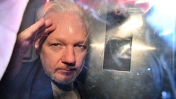 WikiLeaks founder Julian Assange gestures from the window of a prison van as he is driven out of Southwark Crown Court in London on May 1, 2019, after having been sentenced to 50 weeks in prison for breaching his bail conditions in 2012. - A British judge on Wednesday sentenced WikiLeaks founder Julian Assange to 50 weeks in prison for breaching his bail conditions in 2012. Assange took refuge in Ecuador's London embassy to avoid extradition to Sweden and was only arrested last month after Ecuador withdrew his asylum status. (Photo by Daniel LEAL-OLIVAS / AFP) (Photo credit should read DANIEL LEAL-OLIVAS/AFP via Getty Images)