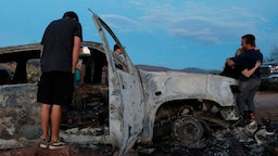 "Members of the Lebaron family look at the burned car where part of the nine murdered members of the family were killed and burned during an ambush in Bavispe, Sonora mountains, Mexico, on November 5, 2019. - US President Donald Trump offered on November 5 to help Mexico ""wage war"" on its cartels after three women and six children from an American Mormon community were murdered in an area notorious for drug traffickers. (Photo by HERIKA MARTINEZ / AFP) (Photo by HERIKA MARTINEZ/AFP via Getty Images)"