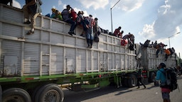 Central American migrants -mostly Hondurans- taking part in a caravan heading to the US, descend from a truck, on arrival at a temporary shelter in Irapuato, Guanajuato state, Mexico on November 11, 2018. - The trek from tropical Central America to the huge capital of Mexico is declining the health of the migrant caravan that endures extreme climate changes, as well as overcrowding and physical exhaustion, and still has to face the desert that leads to the United States. (Photo by ALFREDO ESTRELLA / AFP) (Photo credit should read ALFREDO ESTRELLA/AFP via Getty Images)