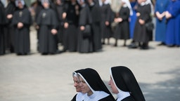 KRAKOW, POLAND - 2018/05/31: Three nuns take a rest under a tree during the Corpus Christi procession in Krakow. The Feast of Corpus Christi or Body of Christ, is the Roman Rite liturgical solemnity celebrating the real presence of the body and blood of Jesus Christ, the Son of God, in the Eucharist . Corpus Christi takes place 60 days after Easter, and every year the procession starts at Wael Castle and ends at the Main Square.