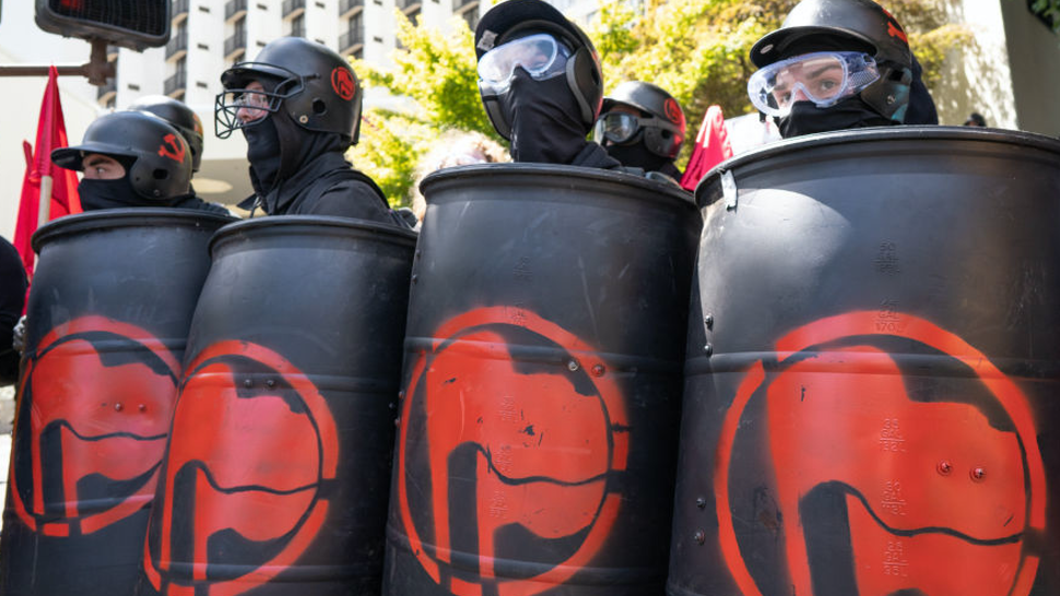 Members of Antifa watch police and far right protesters during the Patriot Prayer Rally.