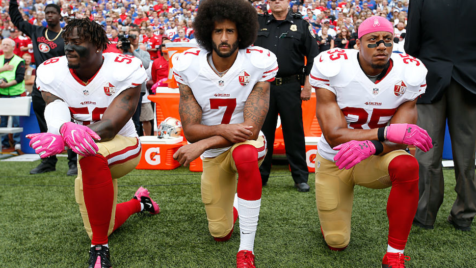 Eli Harold #58, Colin Kaepernick #7 and Eric Reid #35 of the San Francisco 49ers kneel in protest on the sideline, during the anthem, prior to the game against the Buffalo Bills at New Era Field on October 16, 2016 in Orchard Park, New York.