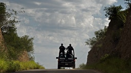 Mexican Federal Police drive through enemy territory south of the Arizona border. From the high embankments on this 2–lane desert road the Beltran–Leyva drug cartel gunmen ambushed and killed 21 Sinaloa Cartel gunmen in July, 2010. (Don Bartletti / Los Angeles Times)