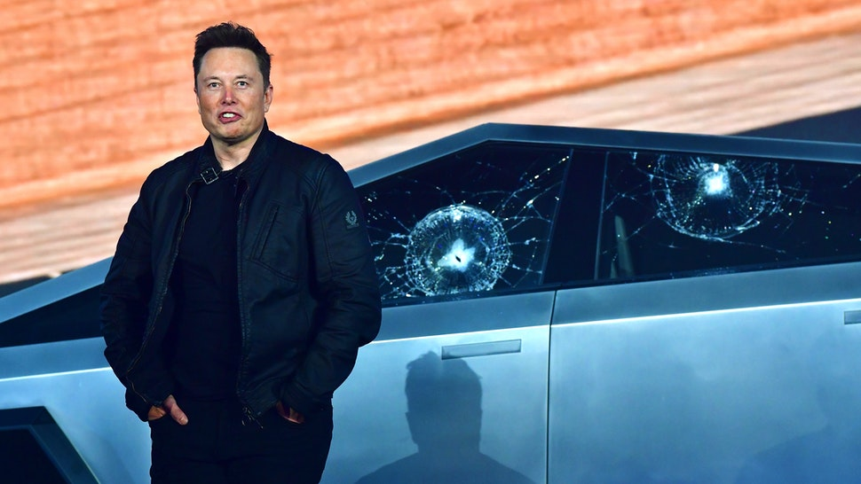 Tesla co-founder and CEO Elon Musk stands in front of the shattered windows of the newly unveiled all-electric battery-powered Tesla's Cybertruck at Tesla Design Center in Hawthorne, California on November 21, 2019.
