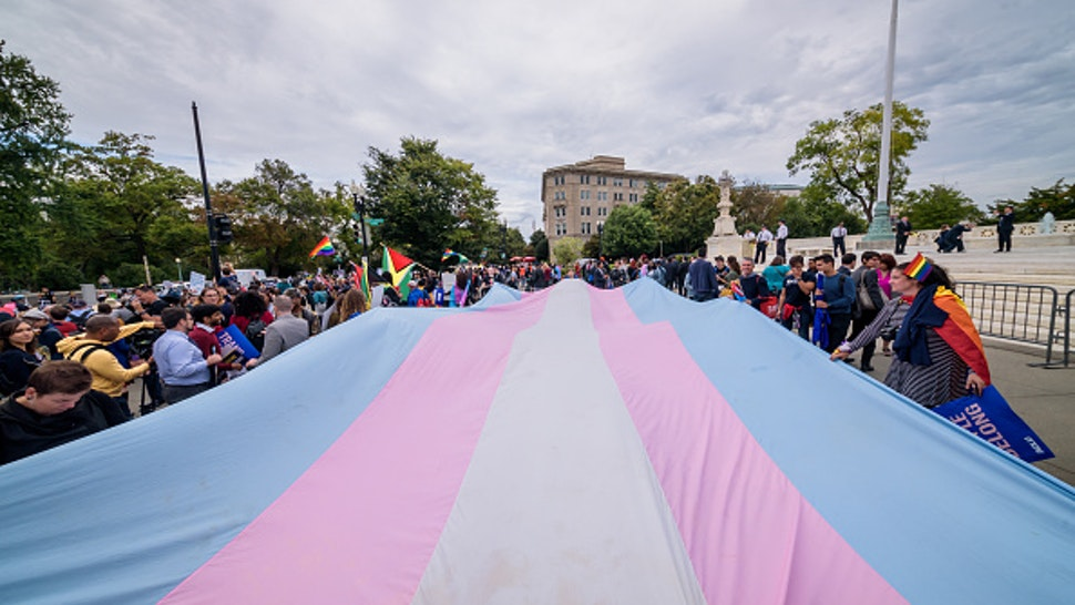 WASHINGTON DC, UNITED STATES - 2019/10/08: A giant Trans Flag unfurled outside the Supreme Court. 133 protesters were arrested blocking the street across the Supreme Court in an act of non violent civil disobedience, as hundreds of LGBTQ+ advocates convened in Washington, DC for a national day of action as a community response to the landmark Supreme Court hearings that could legalize workplace discrimination, primarily against LGBTQ+ people, on the basis of sexual orientation, gender identity, and gender presentation.