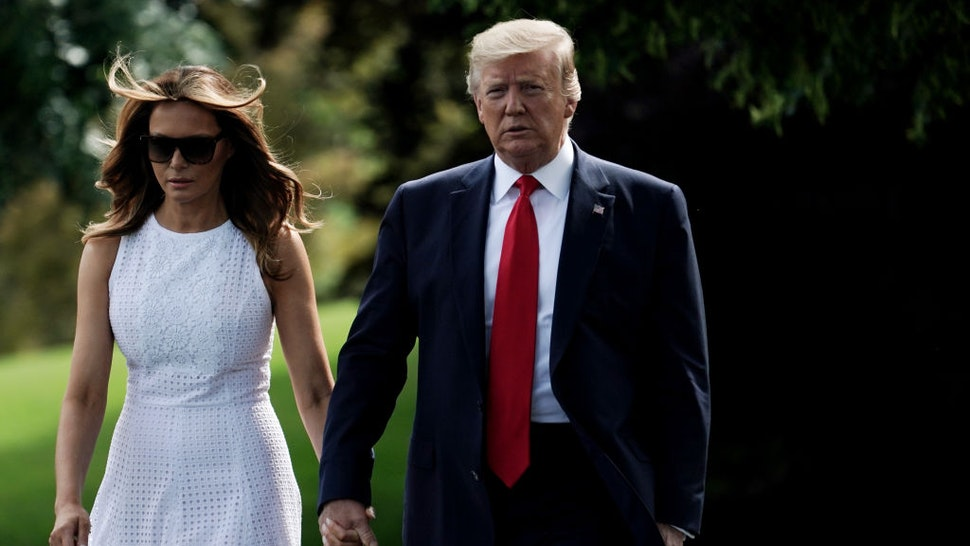President Donald Trump walks with first lady Melania Trump prior to a departure from the White House