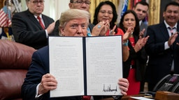 WASHINGTON, DC - NOVEMBER 26: U.S. President Donald Trump displays a signed copy of an executive order establishing the Task Force on Missing and Murdered American Indians and Alaska Natives, in the Oval Office of the White House on November 26, 2019 in Washington, DC. Attorney General William Barr recently announced the initiative on a trip to Montana where he met with Confederated Salish Kootenai Tribe leaders.
