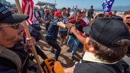 Supporters of President Donald Trump (L) clash with anti-Trump protesters during a rally against his policies in Santa Monica, California on October 19, 2019. - Several people were arrested after fighting and pepper spray was used by the opposing groups.