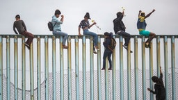 People climb a section of border fence to look toward supporters in the U.S. as members of a caravan of Central American )