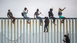 People climb a section of border fence to look toward supporters in the U.S. as members of a caravan of Central American asylum seekers arrive to a rally on April 29, 2018 in Tijuana, Baja California Norte, Mexico.